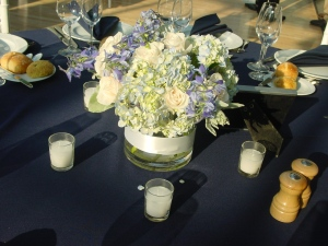 Light blue hydrangeas in lose arrangements stood against the blazing afternoon sun awaiting their romantic candle lit dinner moment.