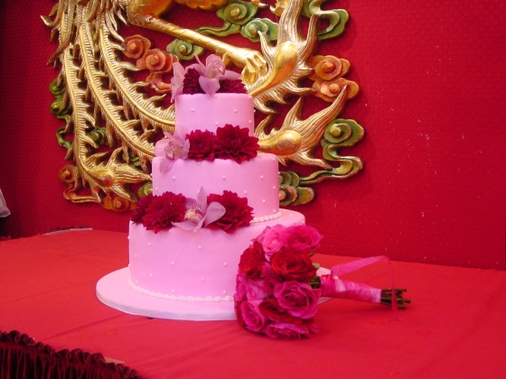The pink cake adorned with cymbidium orchids and dahlias stood next to the throw bouquet with a traditional dragon in the background.