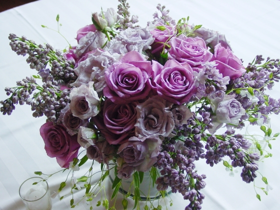 Lilac, Little Blue roses and Blue Bird roses formed this gardeny lavender centerpiece.