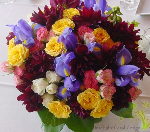 Centerpieces featured black dahlias, yellow and pink baby roses and blue Irises