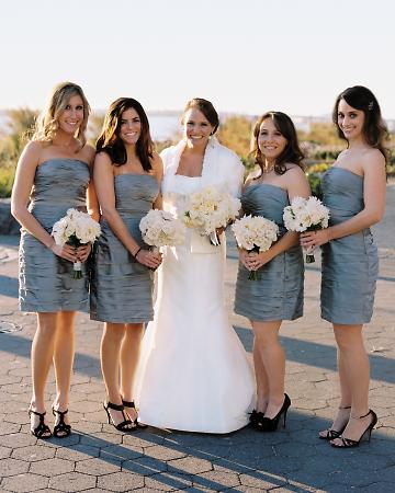 Bridesmaids in gray dresses with white bouquets at Battery Gardens restaurant NYC