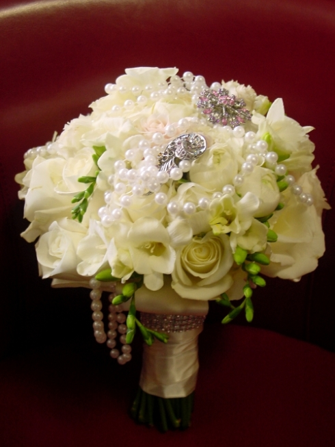 bridal Bouquet of white roses, freesias, ranunculus with braoches and pearl strands by Hoboken Jerey City florist for Nanina's in the park wedding