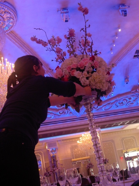 Myer finishing touches on white and pink centerpieces with cherry blossom branches at the Venetian Garfield NJ
