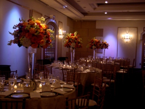 Tall orange arrangements at wedding at Temple Beth Ahm by Jersey CIty Florist