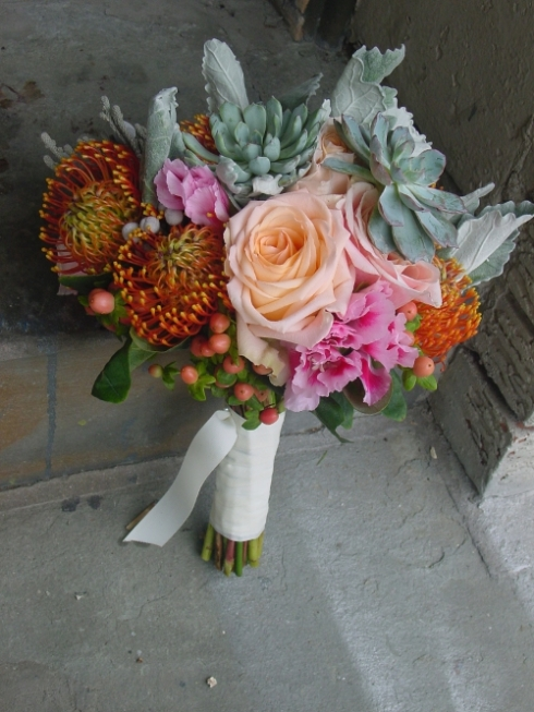 Peach, gray and orange bridal bouquet of pin cushions, lamb ears, succulents and berries