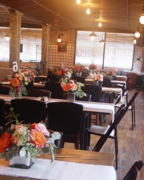 Centerpieces of orange and peach flowers in silver vases in Hoboken NJ Beer Garden Pilsner House