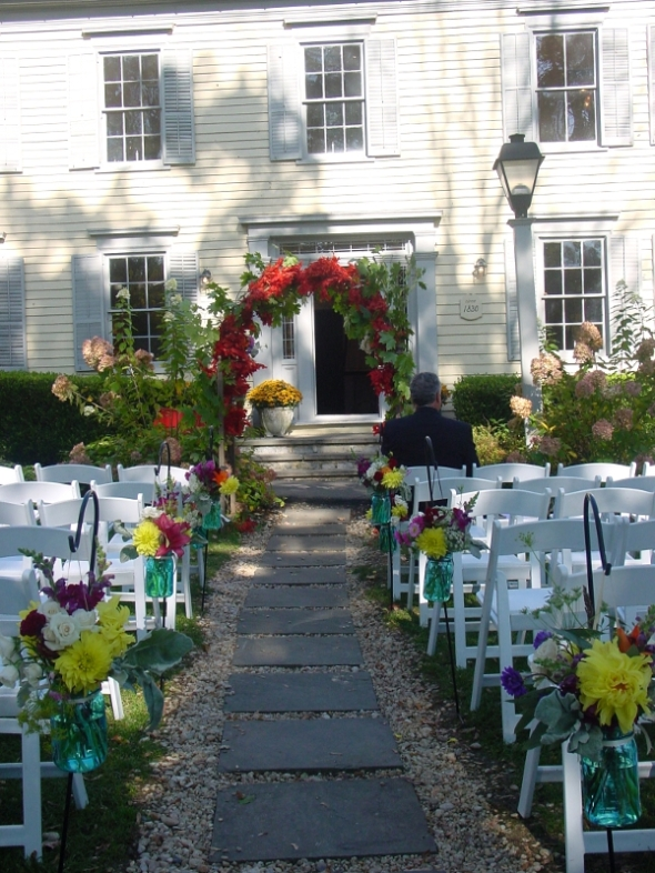Outdoor ceremony with arch autumn arrangements in mason jars along the aisle at Millrace Pond